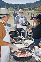 The 21st annual Lincoln County Cowboy Symposium was held in October 2010 at the Ruidoso Downs Racetrack in Ruidoso, New Mexico. Butch Littlejohn of the Camp Cookie Land and Cattle Company is framed by the fixins for the day's meal..
