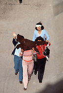 January, 1983. El Paso, Texas. Mexican men and women hide their faces while crossing the Rio Grande River into Texas.