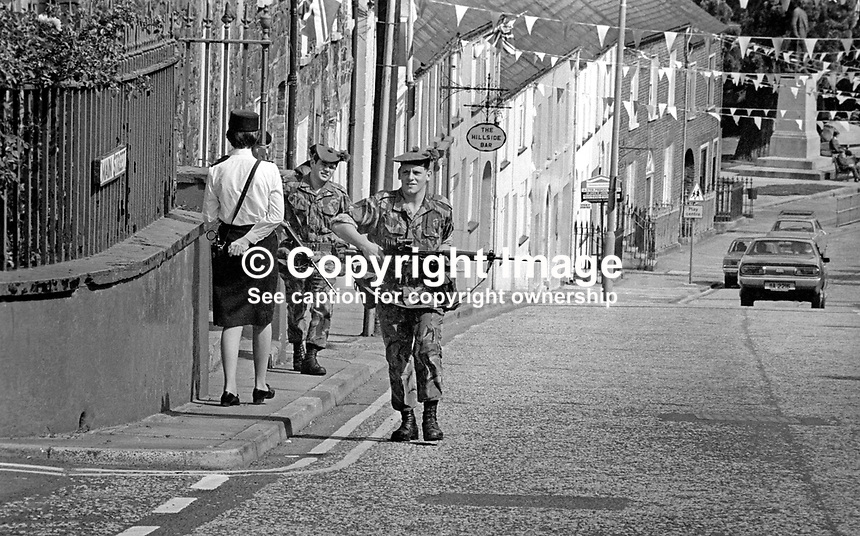 Hillsborough, Co Down, N Ireland, 10th August 1977 - Hillsborough Castle, where visiting royals stays whilst visiting N Ireland is in the centre of this picturesque Ulster village. But the Silver Jubilee visit to the Province of Queen Elizabeth II meant increased security. Normally a constable on the beat would be unusual but for armed soldiers on patrol is a rate occurence. 197708100074f <br />