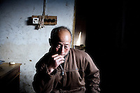 Fan Yu Hao cries as he describes the life of his orphaned grandson Fan Wen Jie, 11, who lives with him and his wife in Fanzhuan Village, Jiangsu Province, China. The boy's father died in a car crash in 2005, and his mother remarried in 2006, abandoning the boy, though she still periodically sends money to help the family.  The boy's grandparents are frequently ill, and the meager income from farming cannot support him.   ..At the time of the picture, China's Amity Foundation charity, was investigating the family's situation in preparation to raise money to financially support these children and other orphans in similar situations.  With Amity's support, each orphan, aged 6-12, would receive approximately 1,400 RMB annually (about 200 USD) to pay for the cost of living. Amity works to keep children out of the institutional orphanages in China, preferring to provide monetary assistance that can help maintain a family environment for the orphans it helps.