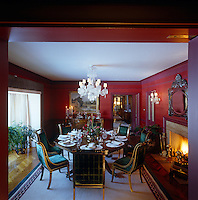 The warm tones of plum and aubergine on the walls constrast with the emerald green velvet of the Empire-style dining chairs in this intimate dining room