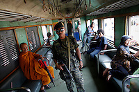 Armed security personnel walk among Thai Buddhist and Muslim passengers on the train they secure between troubled Yala and Pattani provinces in southern Thailand February 28, 2011. Separatists are blamed for most of the attacks on Thailand's predominantly Muslim deep south, which often target Buddhists and Muslims associated with the Thai state, such as police, soldiers, government officials and teachers. No credible group has claimed responsibility for near daily drive-by shootings and bombings, which continue unabated, despite a massive counterinsurgency effort. Yala and Pattani are two of three Muslim-dominated provinces bordering Malaysia where more than 4,300 people, both Muslims and Buddhists, have been killed in a low-level insurgency since 2004.   REUTERS/Damir Sagolj (THAILAND)