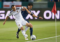 CARSON, CA – May 14, 2011: LA Galaxy midfielder Landon Donovan (10) and Sporting KC defender Roger Espinoza (15) battle for the ball during the match between LA Galaxy and Sporting Kansas City at the Home Depot Center in Carson, California. Final score LA Galaxy 4, Sporting Kansas City 1.
