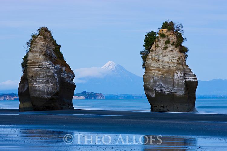Sea stacks with Mount Taranaki (Mount Egmont) in background; North Taranaki Bight; dawn, North Island, New Zealand