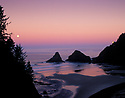 Heceta Head Lighthouse and full moon setting over ocean; Devils Elbow State Park, Oregon coast.