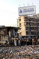 Dharavi residents go about their business in the early morning sun. Many areas of the slum are covered in a sea of plastic rubbish.