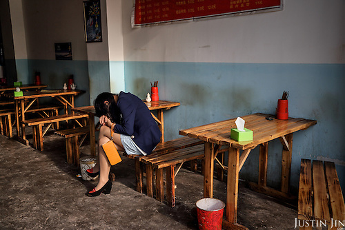 A woman from the country side falls asleep during work in a restaurant in the heart of a relocation housing estate in China's southwestern Chongqing city. <br /> <br /> She, like her clients, were recently relocated from nearby villages that were razed by the government to make way for urban high-rises. <br /> <br /> China is pushing ahead with a dramatic, history-making plan to move 100 million rural residents into towns and cities between 2014 and 2020 &mdash; but without a clear idea of how to pay for the gargantuan undertaking or whether the farmers involved want to move.<br />