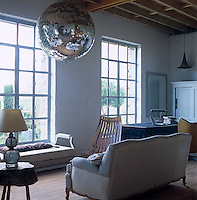 A large disco ball hangs from the ceiling of this pared down living room