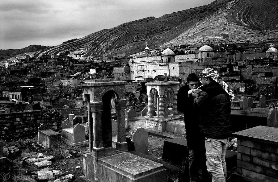 al kosh, northern iraq, january 2005: boys steal a smoke at the ancient assyrian cemetary overlooking the city of al kosh<br />