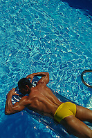 Tan Muscular Man in a speedo resting on a raft in a swimming pool