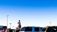 Festival goers gather in a parking lot to be led to Camp Sayso.