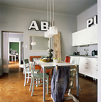 The walls of the kitchen/dining room are painted in a soft grey. The simple table and chairs in the centre of the room provide informal dining