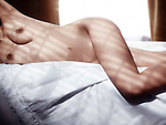 Artistic nude photo of woman body on white sheets