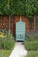 Beehive in beautiful garden with flowering plants Achillea, Nepeta, Verbascum, fence, garden walk path