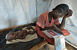 Nyanthem Mayol stares at photos of her relatives while her baby daughter Sara sleeps at her side in a temporary shelter near Ajuong Thok, South Sudan, to where they fled after fighting broke out in their home town of Bentieu in late 2013. The mother and daughter arrived here in March 2014, after weeks of walking through the bush. Displaced families here are living with their relatives on the edge of a camp filled with thousands of refugees from Sudan's Nuba Mountains.