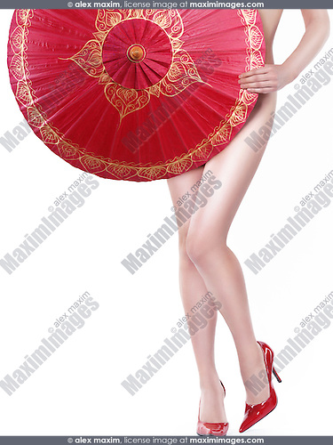 Sexy young nude asian woman covering her body with a red oriental umbrella. Isolated on white background.