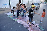 A man and a group of children dance on a sheet which has a picture of Gaddafi on it, on a street in Tripoli. After a six month revolution, rebel forces finally managed to break into Tripoli and have taken control of Bab al-Aziziyah, Col Gaddafi's compound and residence. Few remain that are loyal to Gaddafi in the city; it is seeming that the 42 year regime has come to an end. Gaddafi is currently on the run.