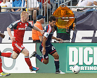 New England Revolution forward Benny Feilhaber (22) dribbles down the wing as Toronto FC defender Richard Eckersley (27) defends. In a Major League Soccer (MLS) match, Toronto FC defeated New England Revolution, 1-0, at Gillette Stadium on July 14, 2012.