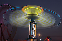 AUGUSTA, NJ - AUGUST 13: The colorfully illuminated Yo Yo spins in front of the Gentle Giant Ferris Wheel against the night sky during the New Jersey State Fair on August 13, 2010 at the Sussex County Fairgrounds, Augusta, New Jersey