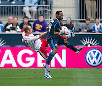 Joel Lindpere (20) of the New York Red Bulls crosses the ball past Amobi Okugo (14) of the Philadelphia Union during the game at PPL Park in Chester, PA.  New York defeated Philadelphia, 3-0.