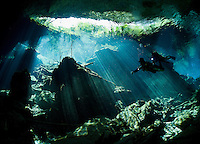 RX0615-D. scuba divers (model released) swims into a curtain of light shining down through the opening to a cenote, the entranceway to caverns and tunnels waiting to be explored. Riviera Maya, Yucatan Peninsula, Mexico.<br /> Photo Copyright &copy; Brandon Cole. All rights reserved worldwide.  www.brandoncole.com