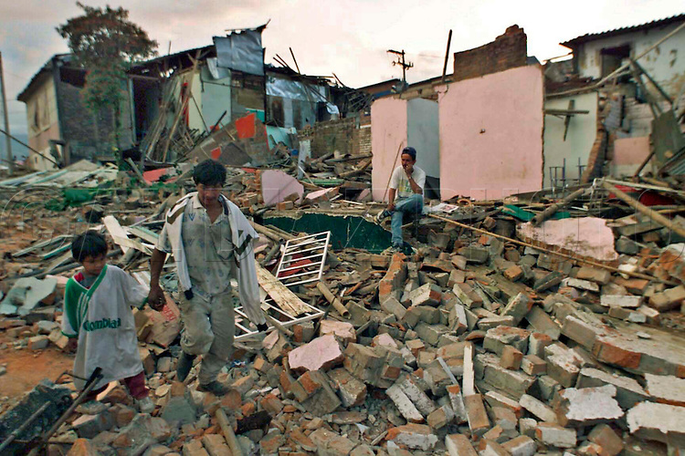 1/26/98 AL DIAZ/MIAMI HERALD--Jose Hernando,6, walks with his father Jose Elize Guaran walks with his father through the rubble of their neighborhood after earthquake in Armenia, Colombia. At right is Jaime Diaz sitting in front of his demolished home.