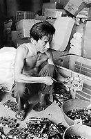 China. Province of Guangdong. The village of Nanyang is part of the town of Guiyu. A male worker, stripped to the waist, takes down by hand electronic components from printed and integrated circuits of old computers. The various parts will be recycled for its metals, chips,... © 2004 Didier Ruef