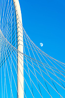 This is a cityscape image we capture of the moon right next to the arch of the bridge as the sun was setting over the Margaret Hunt Hill Bridge and as it was picking up the golden glow of the sunset.