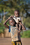 A girl carries her younger sibling in the Makpandu refugee camp in Southern Sudan, 44 km north of Yambio, where more that 4,000 people took refuge in late 2008 when the Lord's Resistance Army attacked their communities inside the Democratic Republic of the Congo. Attacks by the LRA inside Southern Sudan and in the neighboring DRC and Central African Republic have displaced tens of thousands of people, and many worry the attacks will increase as the government in Khartoum uses the LRA to destabilize Southern Sudan, where people are scheduled to vote on independence in January 2011. Catholic pastoral workers have accompanied the people of this camp from the beginning.