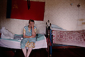 Vodyuga, Russia<br /> July, 1998<br /> <br /> 62 year old  Liza Shestakova sits on her bed under a Soviet flag taken by her son from a disco-tech.