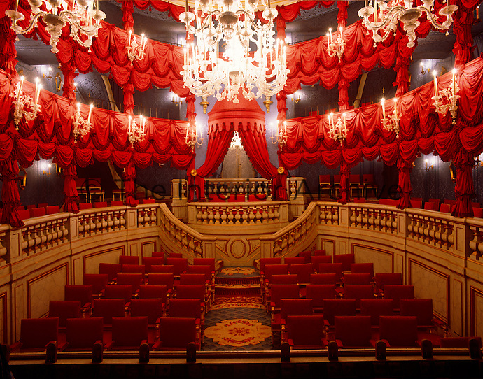 A private theatre is dressed with red curtains and bright crystal chandeliers