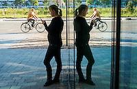 Nederland, Amsterdam, 1 okt  2013<br /> Medewerkster van bedrijf staat buiten te roken en iets te doen met haar smartphone. <br />  Foto(c): Michiel Wijnbergh