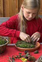 Kinder basteln Zwergengärtchen, Zwergen-Gärtchen aus Naturmaterialien, Bastelei, Tonschale wird mit Moos ausgelegt, Rinde, Eicheln, Kastanien, Äste und Blätter liegen zum Dekorieren bereit