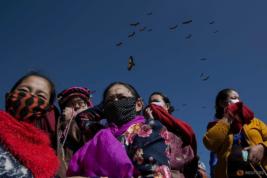 """Ethnic Tibetan people protect themselves from the smell of decomposing body as vultures come from skies during a sky burial near the Larung valley located some 3700 to 4000 metres above the sea level in Sertar county, Garze Tibetan Autonomous Prefecture, Sichuan province, China October 31, 2015. In early afternoons, on a hill near famous Larung Wuming Buddhist Institute relatives and onlookers gather for sky burials in which bodies of deceased people are offered to vultures to prey upon it. Such burials are practiced by some Tibetans and Mongolian in China as an extreme type of Buddhist's """"self-sacrifice almsgiving"""". It is believed that feeding vultures with decomposed corpse of relatives on top of a mountain is a respectful to pay tribute to their passed-away beloved ones. Picture taken November 1, 2015.  REUTERS/Damir Sagolj"""