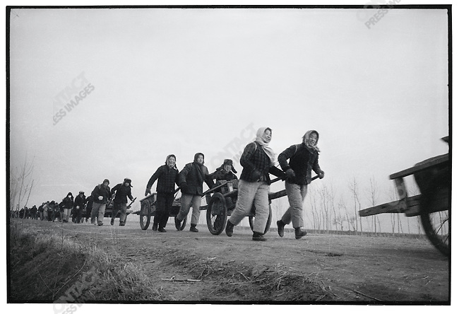 During winter, educated female youth and local peasants pull wheelbarrows on an irrigation project on Chaoyang Commune; Shuangcheng County, Heilongjiang Province, December 17, 1974