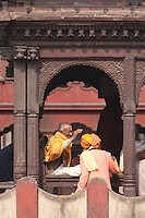 Pashupatinath, Nepal.  Sadhu, a Hindu Ascetic or Holy Man, Blesses a Worshipper.