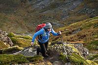 Female hiker hikes trail in mountain landscape, Reinebringen, Lofoten Islands, Norway