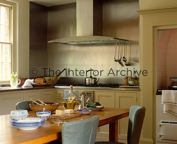 There is an interesting juxtaposition of old-fashioned Aga and contemporary stainless steel wall in this elegant and functional kitchen