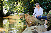 NWA Democrat-Gazette/DAVID GOTTSCHALK - Vickie Kelley, founder and outreach of Natural State Burial Association, sits on a large tree trunk washed against a low water bridge on the property of Don Austin off of Hamestring Creek Road in Fayetteville Thursday, July 16, 2015. The 20 acres of property will become a natural burial cemetery.