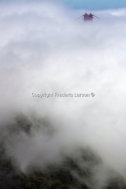 The summer fog makes its way under the Golden Gate Bridge as seen from the Main Headlands of Sausalito, California.