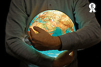 Mature man holding illuminated globe in arms, mid section, close-up (Licence this image exclusively with Getty: http://www.gettyimages.com/detail/200502963-001 )