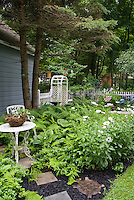 Shade garden with ferns, hostas, pachysandra, white wrought iron patio furniture, blue gazing ball globe, blue house, mulch and stone pathway, hanging pots, planters containers, birdbath, turtle stepping stone