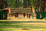 Asia, Bhutan, Thimpu. Archery is the national sport of Bhutan. The target is on the small white board at the end of the field surrounded by opposing team members as a distraction.