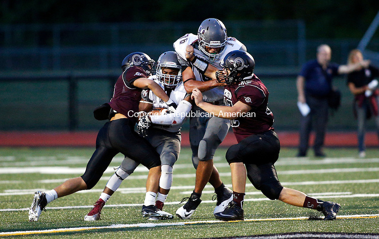Torrington, CT- 25 September 2015-092515CM15- Naugatuck's Antoine Sistrunk carries the ball, as Torrington's Justin Egliskis, left, and Nate Bresson, right, tries to take him down during their NVL matchup in Torrington on Friday.   Blocking is Naugatuck's Logan Bond  (76).      Christopher Massa Republican-American