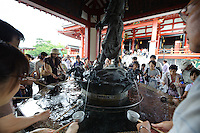 Visitors purifying their hands and mouths with water before approaching the main hall of Sensoji temple, Asakusa, Tokyo, Japan, August 28, 2011. Sensoji is one of the oldest temples in Tokyo, and the shopping arcades around it have sold visitors souvenirs for centuries.