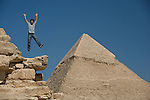A male tourist jumps into the air with joy at the Pyramids of Giza near Cairo, Egypt.