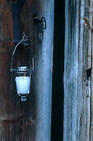 A delicate candle lantern made of clear glass and wire hangs from an antique handle on the weathered front door of a traditional Finnish log cabin