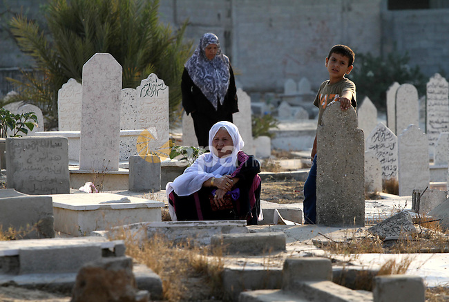 Palestinians visit their relatives' graves in a cemetery during the first day of Eid al-Fitr in Gaza city on August 30, 2011. Eid al-Fitr marks the end of the Muslim holy month of Ramadan. Photo by Mohammed Asad