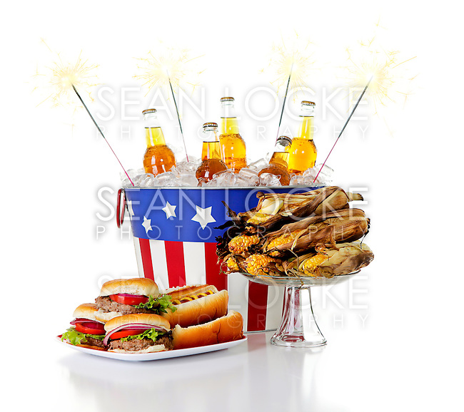 Series with lots of summertime food - beer on ice, grilled corn, hot dogs and watermelon.  Isolated on white background.