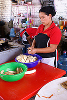 Young Honduran woman slicing plantains in a restaurant, Santa Rosa de Copan, Honduras.